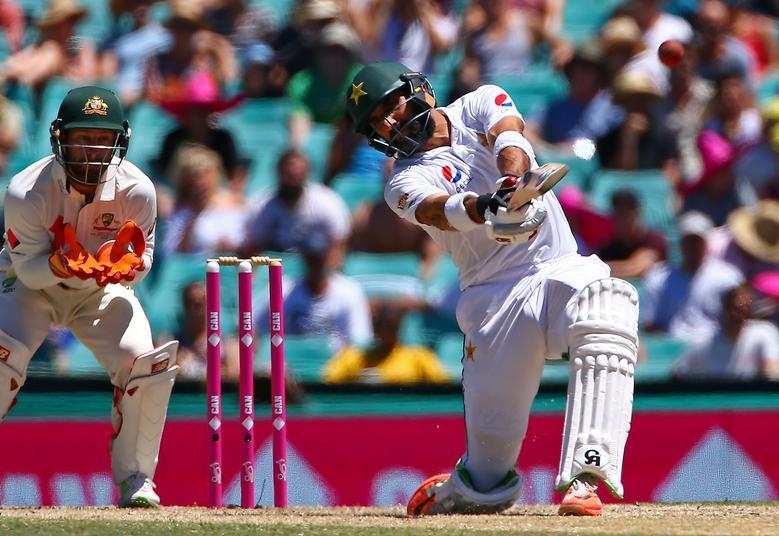 Pakistan's Sarfraz Ahmed hits a six as Australia's wicketkeeper Matthew Wade looks on.       REUTERS/David Gray