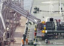 Imagen de archivo de empleados portuarios supervisando una carga de crudo en un tanquero en el puerto de Kuwait. 3 abril 2006. Es poco probable que la OPEP cumpla en su totalidad los objetivos de recortes de producción de petróleo, a pesar de que Arabia Saudita ha anunciado que disminuyó su bombeo en más de lo prometido, de acuerdo a delegados del grupo de países exportadores.REUTERS/Stephanie McGehee