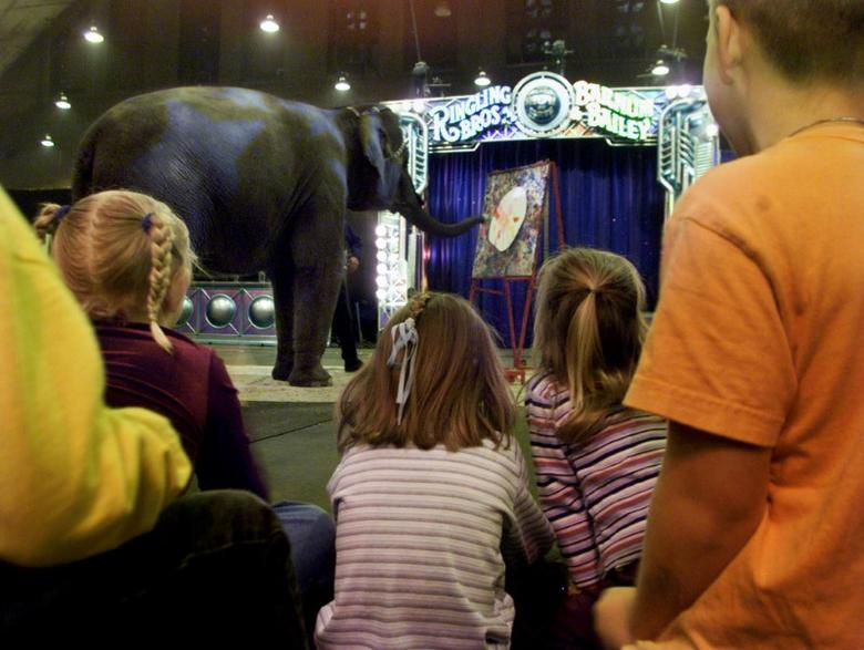 Children watch Kelly Ann the Elephant paint an Easter egg, at theRingling Bros. And Barnum and Bailey Circus in Washington, April 11,2003. The children were from area military families taking part in amilitary appreciation day at the circus. REUTERS/William PhilpottWP - RTRLPW5