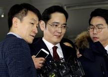 Jay Y. Lee (centre), le numéro un du groupe Samsung, arrive pour être interrogé en tant que suspect dans l'affaire de trafic d'influence autour de la présidente sud-coréenne Park Geun-hye. Le procureur spécial chargé de l'enquête demandera pour lui un mandat d'arrêt. /Photo prise le 12 janvier 2017/REUTERS/Ahn Young-joon