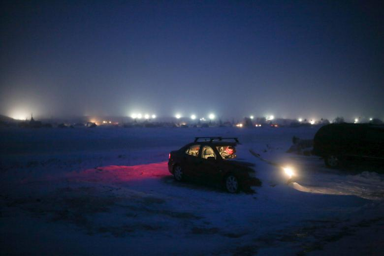 A woman is seen sitting inside her vehicle during dusk in the Rosebud camp where