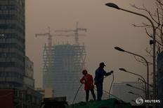 En la imagen, dos trabajadores en una obra en Pekín el 6 de diciembre de 2016. ELa economía China probablemente se expandirá un 6,5 por ciento este año, a medida que las autoridades toleren una mayor desaceleración mientras se focalizan en contener los crecientes riesgos fiscales, aunque un debilitado yuan complicaría sus alternativas de política monetaria, mostró un sondeo de Reuters.REUTERS/Thomas Peter