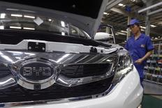 A worker stands behind a car manufactured at a BYD assembly line in Shenzhen, China May 25, 2016.   REUTERS/Bobby Yip