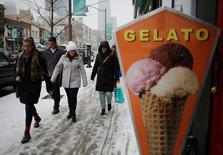 People bundled up in winter clothing pass an ice cream shop during a snowfall in midtown Toronto, Ontario, Canada December 11, 2016. REUTERS/Chris Helgren
