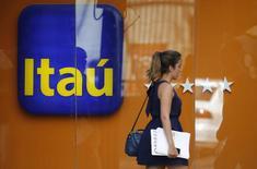 Una mujer camina frente al logo de Itaú en Río de Janeiro, Brasil.29 de enero 2014.El banco Itaú Unibanco anunció el viernes que llegó a un acuerdo para aplazar a enero de 2022 la adquisición de acciones de CorpBanca en Colombia, que daría al conglomerado financiero brasileño la quinta posición entre los bancos minoristas colombianos. REUTERS/Sergio Moraes (BRAZIL - Tags: BUSINESS) - RTX18001