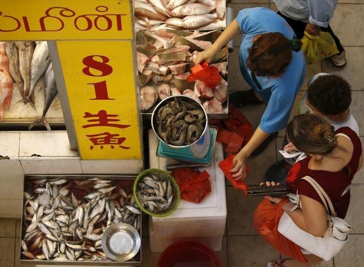 People shop for fish at a wet market in Singapore March 23, 2016. REUTERS/Edgar Su/File Photo