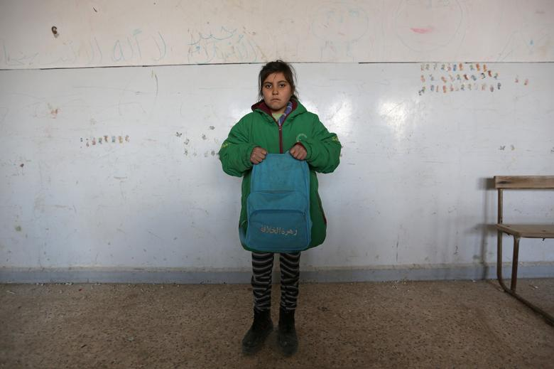 The students, aged 5-15, were given notebooks and pens on their first day back on Monday by seven volunteers who teach reading, writing and maths and helped get the school habitable again over the past six weeks.  REUTERS/Khalil Ashawi
