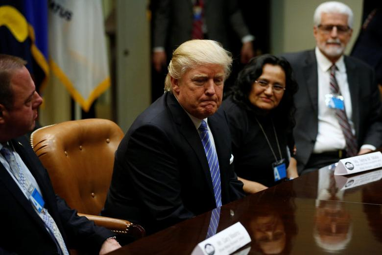 U.S. President Donald Trump, flanked by Gary Masino (L) of the Sheet Metal Workers Union, Telma Mata (2nd R) of the Heat and Frost Insulators Allied Workers Local 24 and United Brotherhood of Carpenters General President Doug McCarron (R), holds a roundtable meeting with labor leaders at the White House in Washington, U.S. January 23, 2017.  REUTERS/Jonathan Ernst