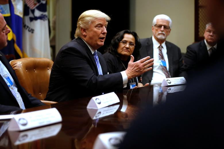 U.S. President Donald Trump (C), flanked by Gary Masino (L) of the Sheet Metal Workers Union, Telma Mata (2nd R) of the Heat and Frost Insulators Allied Workers Local 24 and United Brotherhood of Carpenters General President Doug McCarron (R), holds a roundtable meeting with labor leaders at the White House in Washington, U.S. January 23, 2017.  REUTERS/Jonathan Ernst