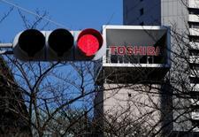 El consejo de administración de Toshiba Corp se reunirá el viernes para aprobar planes para segregar su negocio de semiconductores y espera recaudar más de 200.000 millones de yenes vendiendo una participación del 20 por ciento en el mismo, dijo una fuente con conocimiento directo del asunto. En la imagen, el logo de Toshiba Corp se ve tras un semáforo en su sede de Tokio, el 23 de enero de 2017. REUTERS/Toru Hanai