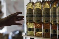 Un hombre alcanza un botella del tquila José Cuervo en Ciudad de México. 11 de diciembre de 2012. La mexicana José Cuervo, la mayor productora de tequila del mundo, podría levantar unos 15,252 millones de pesos (unos 706.5 millones de dólares) con una oferta pública inicial planeada para el mes próximo, de acuerdo con una presentación a inversionistas. REUTERS/Edgard Garrido/Archivo