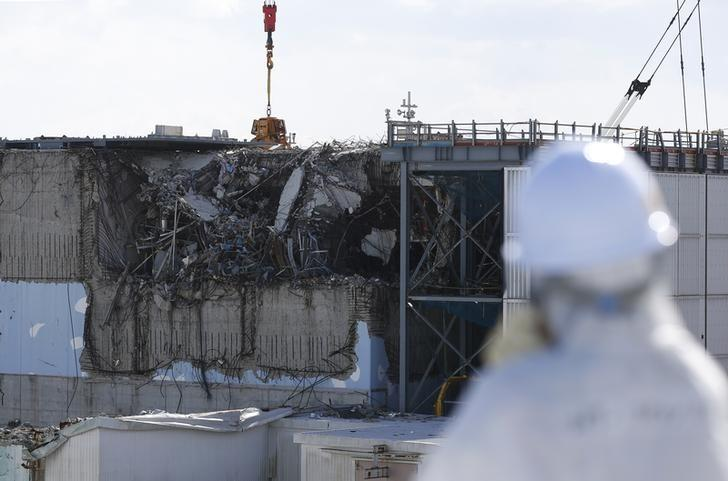 A member of the media, wearing a protective suit and a mask, looks at the No. 3 reactor building at Tokyo Electric Power Co's (TEPCO) tsunami-crippled Fukushima Daiichi nuclear power plant in Okuma town, Fukushima prefecture, Japan February 10, 2016.  REUTERS/Toru Hanai