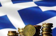 Grecia superó sus objetivos fiscales el año pasado y probablemente logre cumplir los de este año, situándose en el buen camino para conseguir su primer superávit primario en 2018, dijo el vicepresidente de la Comisión Europea, Valdis Dombrovskis. En la image, monedas de euro delante de una bandera de Grecia, el 29 de junio de 2015. REUTERS/Dado Ruvic/File Photo