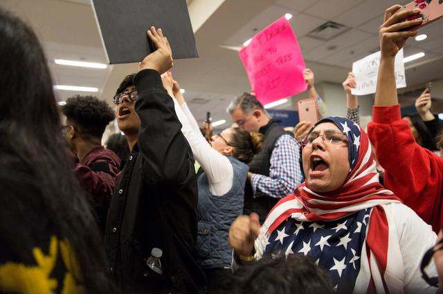 A woman in an American flag hijab chants with other protesters against the travel ban imposed by U.S. President Donald Trump's executive order, at Dallas/Fort Worth International Airport in Dallas, Texas, U.S. January 28, 2017.  REUTERS/Laura Buckman