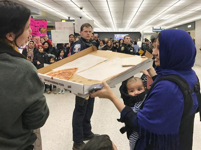 A woman offers pizza to people protesting against the travel ban imposed by U.S. President Donald Trump's executive order, at Washington Dulles International Airport in Dulles. REUTERS/Yeganeh Torbati