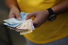 Una persona contando reales en Brasilia, jun 28, 2014. Brasil anotó un déficit presupuestario primario de 70.737 millones de reales (22.700 millones de dólares) en diciembre, mostraron datos del Banco Central publicados el martes.   REUTERS/Ueslei Marcelino
