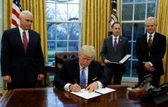 """El principal asesor comercial del presidente Donald Trump acusó a Alemania de usar un euro """"sumamente infravalorado"""" para obtener ventajas competitivas, lo que provocó un rechazo de la canciller Angela Merkel y llevó a la divisa a un máximo de ocho semanas contra el dólar. En la foto, el presidente Donald Trump (al centro) firma un decreto en la Casa Blanca acompañado del jefe del Consejo de Comercio, Peter Navarro (derecha), del vicepresidente Mike Pence (izquierda) y del jefe de gabinete Reince Priebus el 23 de enero de 2017. REUTERS/Kevin Lamarque"""