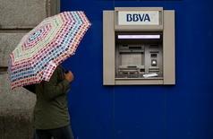 BBVA anunció el miércoles un descenso del beneficio neto correspondiente al cuarto trimestre del año por nuevas provisiones relacionadas con las cláusulas suelo en las hipotecas comercializadas en su red. En la imagen de archivo, una mujer que se cobija bajo un paraguas pasa ante un cajero de BBVA en Madrid, el 4 de abril de 2016. REUTERS/Andrea Comas