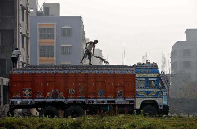 A labourer unloads construction material from a truck next to residential buildings under construction on the outskirts of Kolkata, India, February 1, 2017. REUTERS/Rupak De Chowdhuri