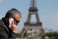 La Unión Europea cerró el miércoles de madrugada un acuerdo preliminar para poner límites a los pagos mayoristas que los operadores de telecomunicaciones se facturan entre sí cuando sus clientes usan el móvil en el extranjero, lo que despeja el camino para la abolición de las tarifas de itinerancia en junio. En la imagen de archivo, un hombre habla por el móvil en la plaza del Trocadero de París con la Torre Eiffel al fondo, el 16 de mayo de 2014. REUTERS/Christian Hartmann