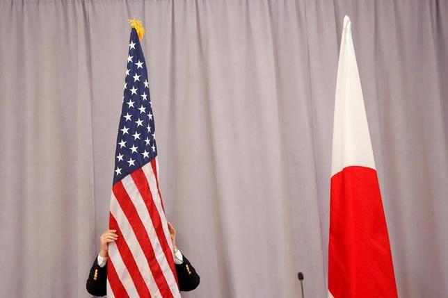 2月2日、日米両政府は、ワシントンで10日に予定している安倍晋三首相とトランプ大統領の首脳会談を翌11日も開催する方針だ。写真は日米の国旗を整える担当者。ニューヨークで昨年11月撮影(2017年 ロイター/Andrew Kelly)
