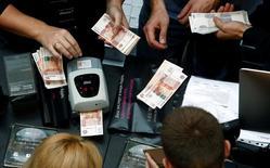 Продавцы в магазине пересчитывают деньги. Минфин РФ в январе 2017 года не тратил средства Резервного фонда на финансирование бюджетного дефицита, следует из сообщения министерства. REUTERS/Sergei Karpukhin
