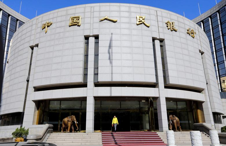FILE PHOTO: A woman walks out of the headquarters of the People's Bank of China (PBOC), the central bank, in Beijing, China November 20, 2013.  REUTERS/Jason Lee/File Photo