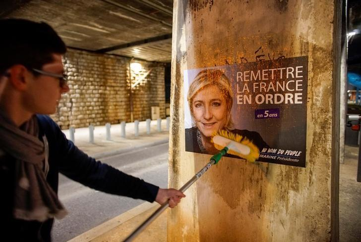 A member of the National Front youths puts up a poster of Marine Le Pen, French National Front (FN) political party leader and candidate for the French 2017 presidential election, ahead of a 2-day FN political rally to launch the presidential campaign in Lyon, France, February 2, 2017. REUTERS/Robert Pratta