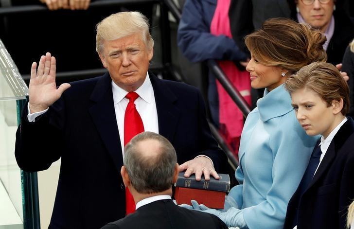 US President Donald Trump takes the oath of office with his wife Melania and son Barron at his side, during his inauguration at the U.S. Capitol in Washington, U.S., January 20, 2017. REUTERS/Kevin Lamarque