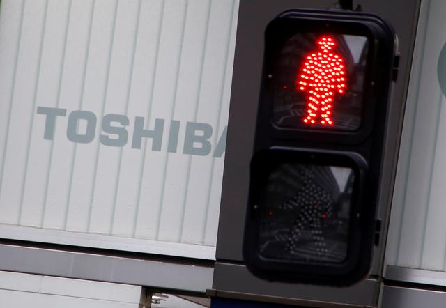 FILE PHOTO -  Toshiba's logo is seen behind a traffic sign at an electronic shop in Tokyo, Japan, November 11, 2016. Picture taken November 11, 2016. REUTERS/Kim Kyung-Hoon/File Photo