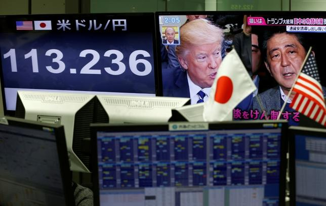 A TV monitor showing U.S. President Donald Trump and Japanese Prime Minister Shinzo Abe is seen next to another monitor showing the Japanese yen's exchange rate against the U.S. dollar at a foreign exchange trading company in Tokyo, Japan, February 1, 2017.  REUTERS/Kim Kyung-Hoon