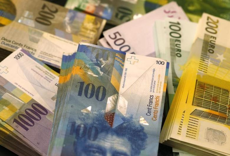 Swiss Franc and Euro banknotes of several values lie on a table in a Swiss bank in Bern November 25, 2014. REUTERS/Ruben Sprich