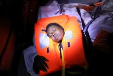 Mata, 23, who's from Nigeria, tries to recover after fainting during a rescue operation of 104 sub-Saharan migrants aboard a raft by the Spanish NGO Proactiva Open Arms, in the central Mediterranean Sea, 24 miles north of the Libyan coastal city of Sabratha, January 27, 2017. REUTERS/Giorgos Moutafis