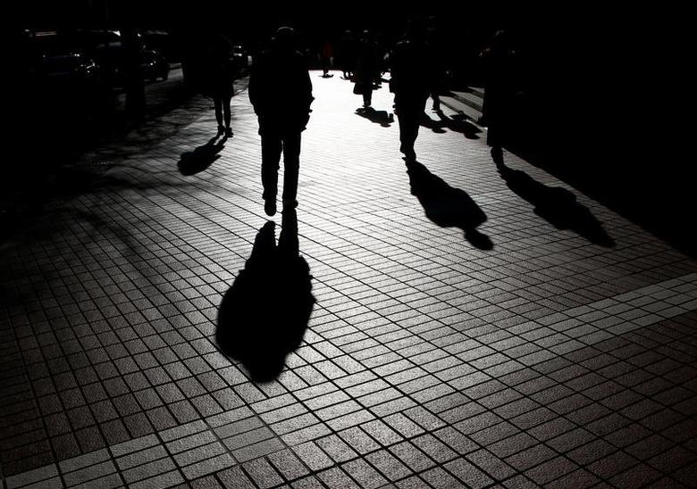 Pedestrians cast shadows as they make their way at a financial district in Tokyo, Japan, January 26, 2017.   REUTERS/Kim Kyung-Hoon