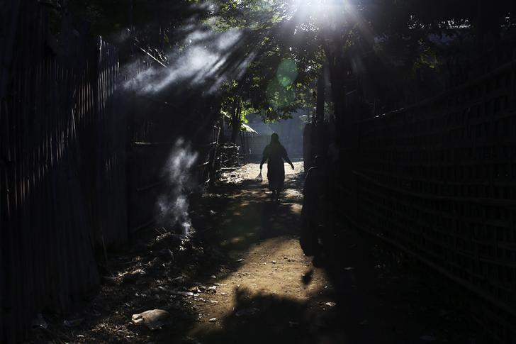 A Rohingya woman walks through Thae Chaung refugee camp outside Sittwe November 13, 2014.  REUTERS/Minzayar