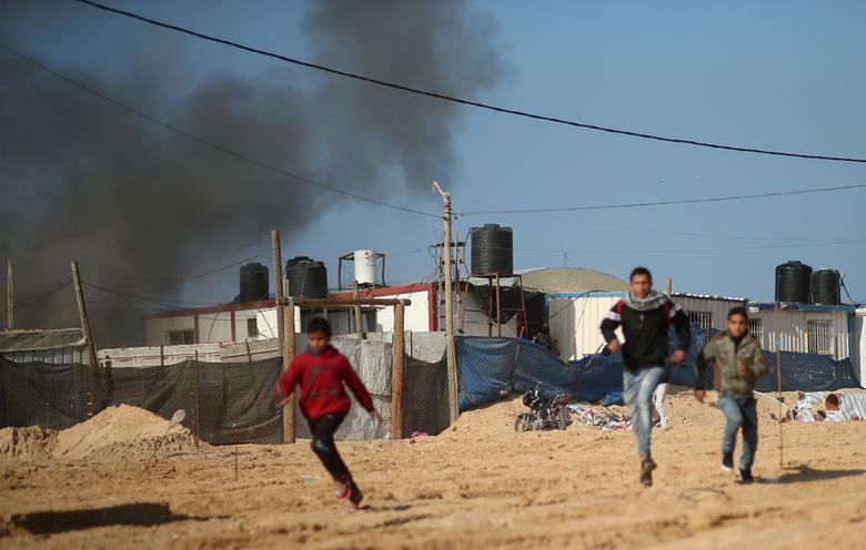 Palestinians run as smoke rises following what police said was an Israeli air strike on a Hamas post, in the northern Gaza Strip February 6, 2017. REUTERS/Mohammed Salem