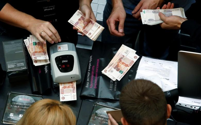 FILE PHOTO: A shop assistant (L) counts Russian rouble banknotes as customers gather at a store selling Apple products during the launch of the new iPhone 7 sales at the State Department Store, GUM, in central Moscow, Russia, September 23, 2016. REUTERS/Sergei Karpukhin/File Photo