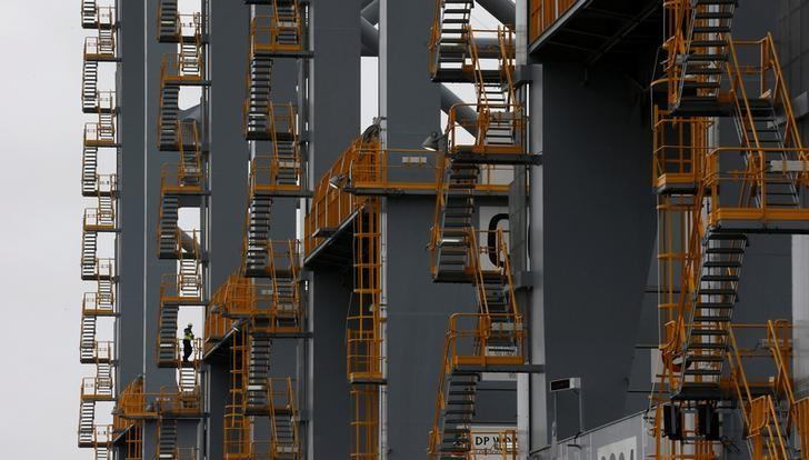 A worker stands in the stairwell of a crane on the quayside at DP World London Gateway container port in Essex, southern England July 30, 2013. REUTERS/Suzanne Plunkett/File Photo