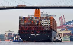 """En la imagen de archivo, barcos remolcadores llevan el barco de contenedores """"Hamburg Express"""" por el puerto de Hamburgo, el 15 de agosto de 2012.Las exportaciones de Alemania subieron menos a lo previsto este año debido a la amenaza de posibles medidas proteccionistas del presidente de Estados Unidos, Donald Trump, dijo el martes el jefe de la asociación comercial y mayorista BGA.REUTERS/Morris Mac Matzen"""