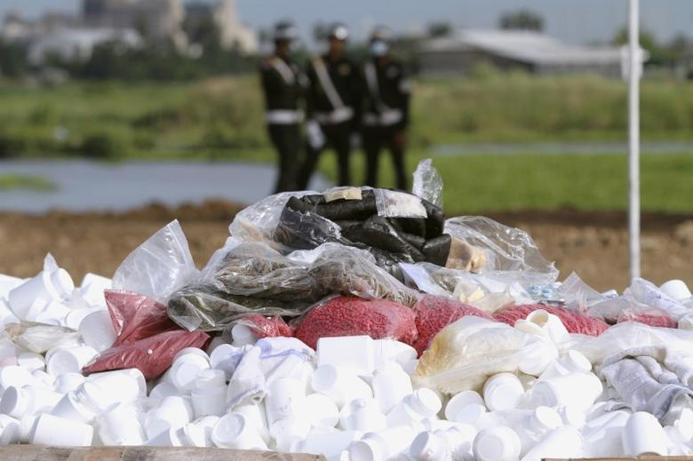 Military police (background) look on during a ceremony to dispose of confiscated drugs, in Phnom Penh August 28, 2012.  REUTERS/Samrang Pring