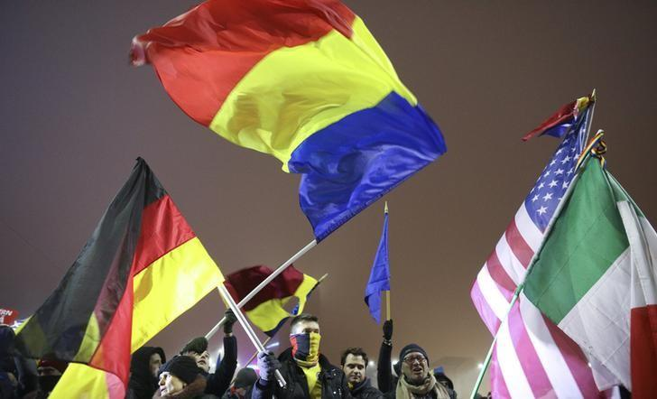 Romanians wave flags of their country and other EU nations during a protest of thousands against the Romanian government in Bucharest, Romania, February 6, 2017.  REUTERS/Stoyan Nenov