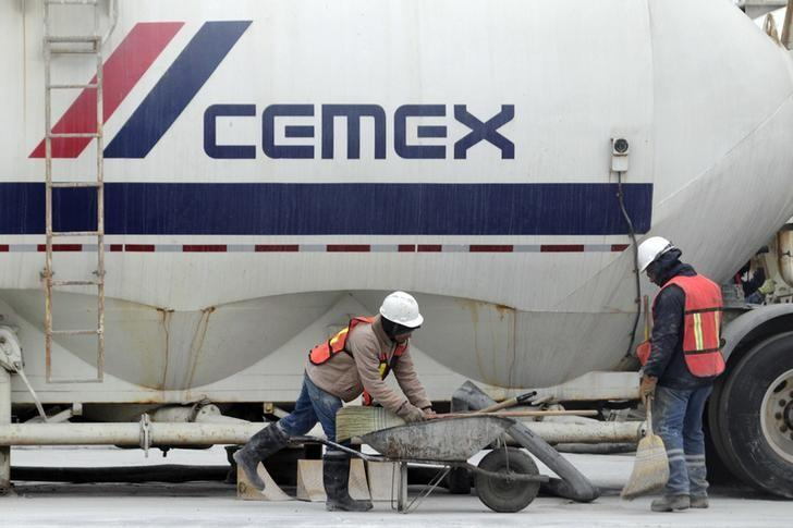 Workers stand in front of a trailer truck at a concrete plant of Mexican cement maker CEMEX, in Monterrey February 24, 2015. REUTERS/Daniel Becerril