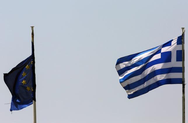 2月9日、ギリシャの閣僚は、国際債権団が支援策の条件となる改革を承認すると楽観しているとの立場を示した。写真はギリシャ(右)とEUの旗、アテネで昨年6月撮影(2017年 ロイター/Yannis Behrakis)