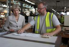 La primera ministra británica, Theresa May (L), habla con un trabajador mientras visita una fábrica de carpintería en Londres, Gran Bretaña. 3 de agosto 2016. Las manufacturas británicas crecieron con más fuerza de lo esperado en diciembre, mostrando que la economía se mantuvo resistente al final del año a pesar del Brexit, aunque el panorama para el 2017 sería más complejo.REUTERS/Neil Hall - RTSKWAQ