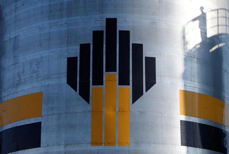 The shadow of a worker is seen next to a logo of Russia's Rosneft oil company at the central processing facility of the Rosneft-owned Priobskoye oil field outside the West Siberian city of Nefteyugansk, Russia, August 4, 2016. Picture taken August 4, 2016. REUTERS/Sergei Karpukhin