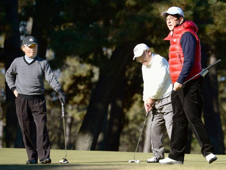 Japan's Prime Minister Shinzo Abe (R) plays golf with Fujio Mitarai (C), former chairman of the Japan Business Federation, and Sadayuki Sakakibara, current chairman, in Chigasaki, Japan, in this photo taken by Kyodo January 3, 2015. Picture taken January 3, 2015.  Mandatory credit Kyodo/via REUTERS ATTENTION EDITORS