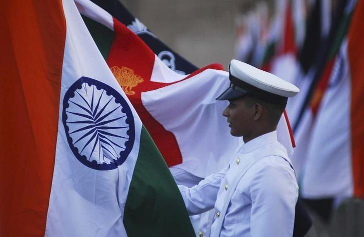 An Indian Navy soldier holds an Indian national flag during a dress rehearsal ahead of Navy Day celebrations in Mumbai, December 2, 2011. Picture taken on December 2, 2011. REUTERS/Stringer/Files