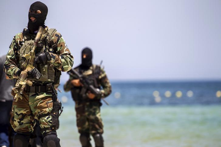 Tunisia's special forces secure the beachside of the Imperial Marhaba resort, while British, French, German and Tunisia's interior minister arrive to pay their tribute in front of a makeshift memorial in Sousse, Tunisia, June 29, 2015. REUTERS/Zohra Bensemra/File Photo
