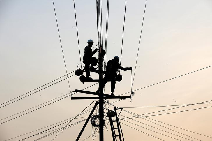 Technicians are silhouetted as they fix cables on a power transmission line in Karachi, Pakistan January 9, 2017. REUTERS/Akhtar Soomro/File Photo