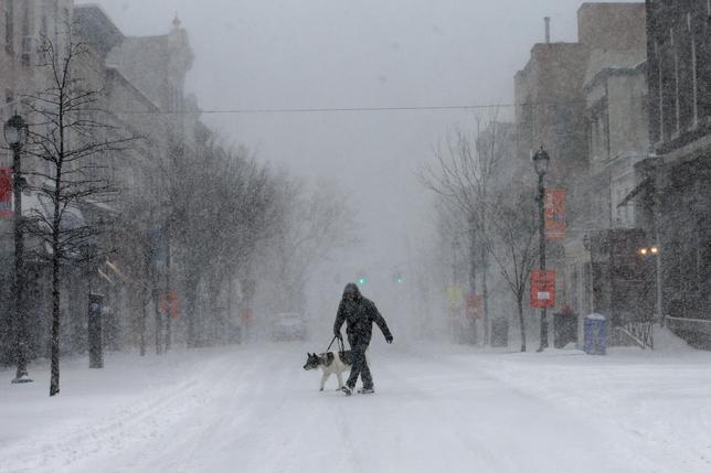 A man walks his dog in heavy falling snow on Main Street in the village of Nyack, New York, a suburb north of New York City, U.S., February 9, 2017. REUTERS/Mike Segar